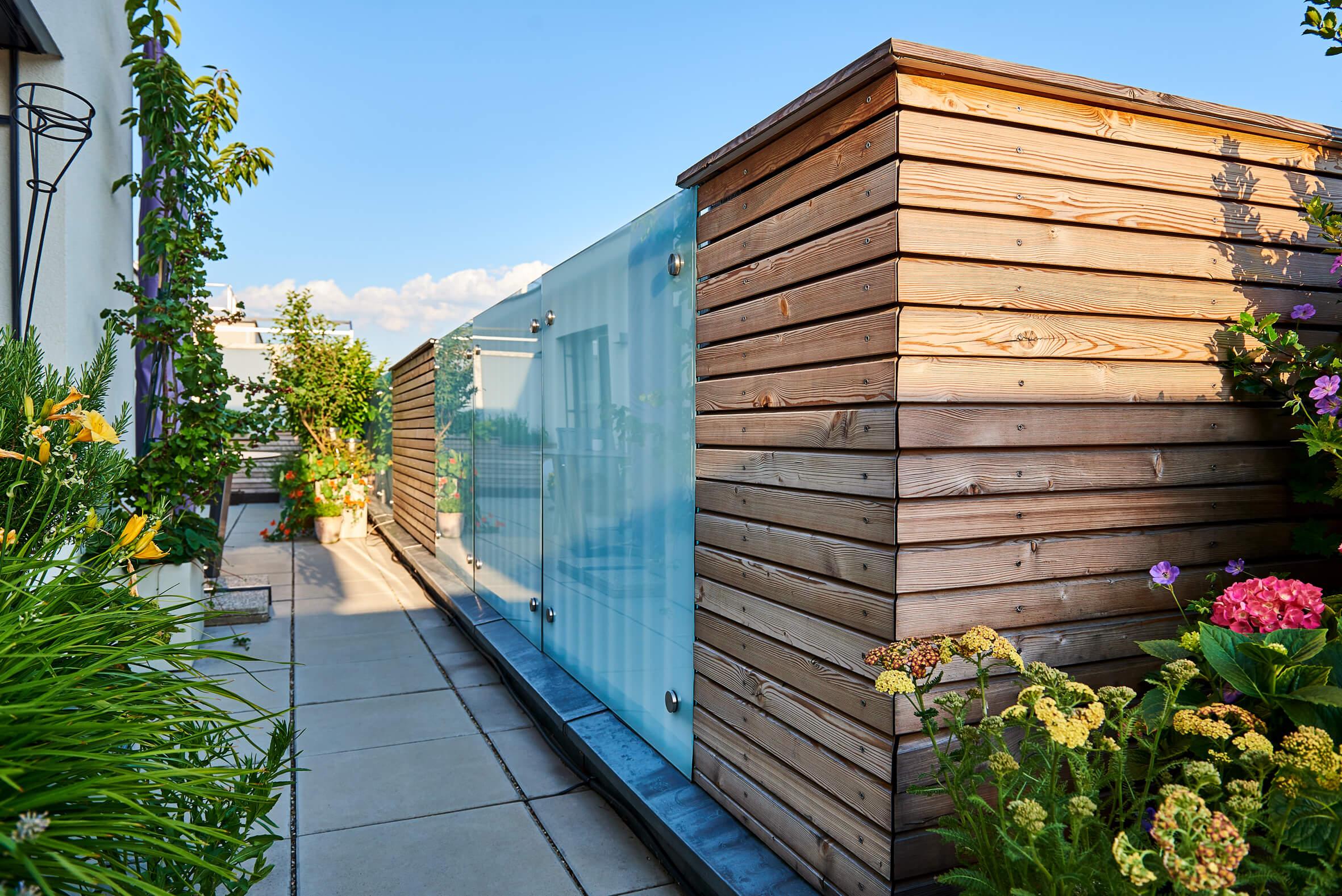 Sichtschutz aus Holz und Glas auf einer Dachterrasse