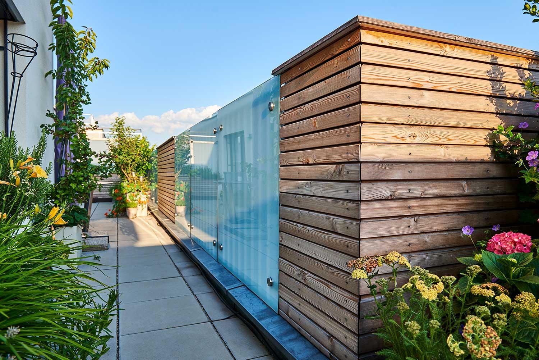 Eine begrünte Dachterrasse mit einer Wand aus Holz und Glaselementen